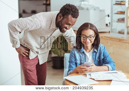 Amusing content. Cheerful young man standing near his female colleague and looking at her phone while she showing him some funny pictures on phone during break at work