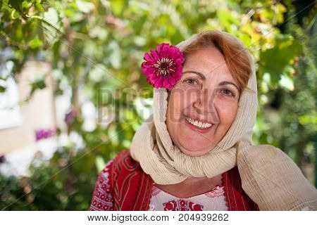 Portrait of a smiling Romanian senior woman in traditional folk costume.