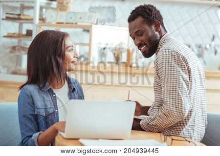 Check it out. Smiling charming woman showing her male colleague the presentation for their project, waiting for his opinion while the man looking at it and making notes
