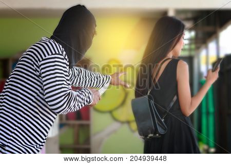Thief stealing a wallet from a woman bag on the street