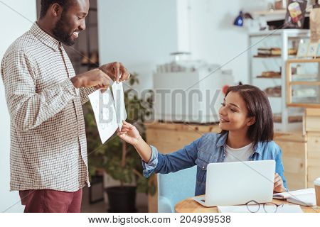 Best option. Charming cheerful young man showing two printouts with project design concepts and the woman choosing one of them