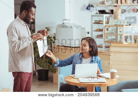 Choose one. Cheerful young man holding two printouts with project design concepts to his female colleague and the woman picking one best option