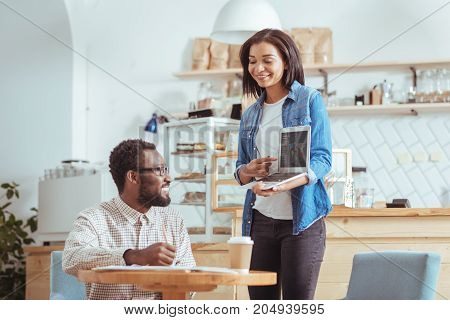 Fresh ideas. Beautiful young woman holding a laptop and giving a presentation about project concept to her male colleague in the coffeehouse