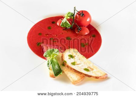 Tomato soup with toast bread in a large white plate