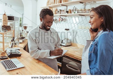 Customer-friendly. Pleasant young barista standing behind the cafe counter and putting down and order being received by phone and dictated by his female colleague