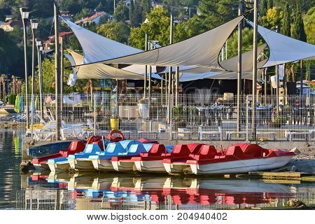Several pedal boats and beach bar in a beautiful summer day