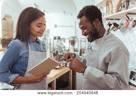 Preparing new place. Charming young woman making notes about necessary supplies and her male colleague scrutinizing portafilter while preparing their new cafe for opening