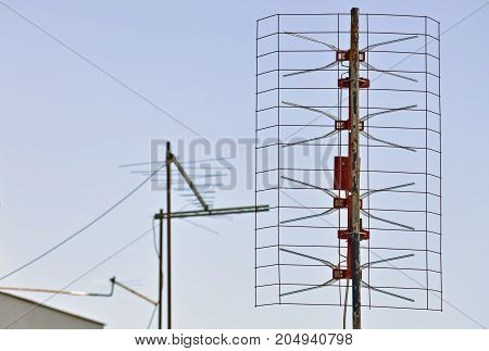 Closeup of an old analog antenna and clear sky in the background