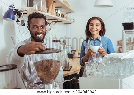 Love our work. Handsome male barista using an espresso machine to make coffee while his female colleague holding a cup of it, tasting the result