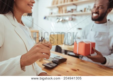 Quality service. The focus being on the hands of a beautiful young woman holding a golden card and being ready to pay for her order in the coffeehouse