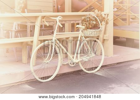 Vintage bicycle decorated by basket with flowers in old stile. Postcard romantic rural concept.