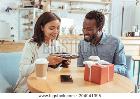 Thorough inspection. Pleasant pretty young woman sitting in the coffeehouse with her best friend and carefully scrutinizing a VR headset together with him