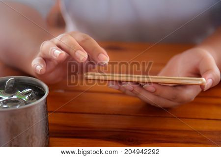 Woman's hand is playing a mobile phone on a wooden table with a glass of water.