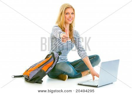 Sitting on floor with schoolbag and laptop smiling teengirl showing thumbs up gesture isolated on wh