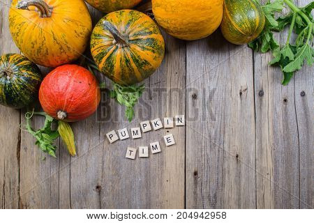 A frame of different pumpkins on an old wooden background, flat lay, top view with  inscription