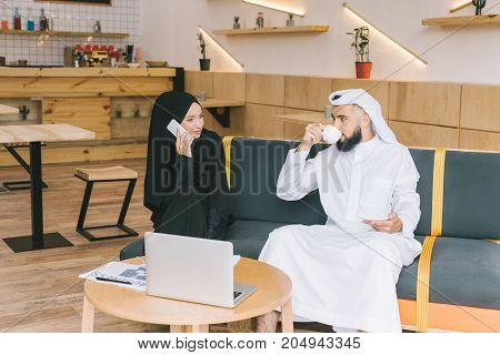 young muslim businesspeople having conversation in cafe