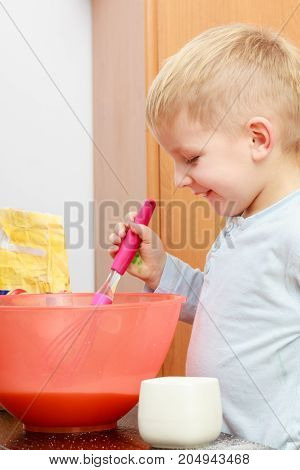 Healthy diet for children youngsters cooking concept. Little kid boy cooking making cake in bowl
