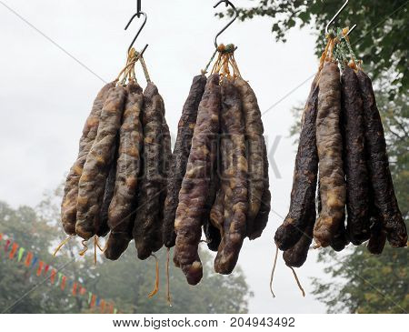 dried sausage hanging outside in the background of trees
