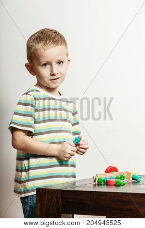 Spending free time play and education for children. Little boy in striped shirt play with colorful toy on table.