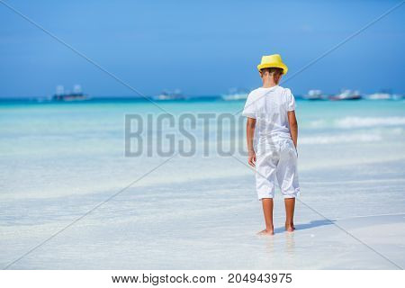 Back view of Little boy wearing white having fun on tropical ocean beach. Kid during family sea vacation. Summer water fun.