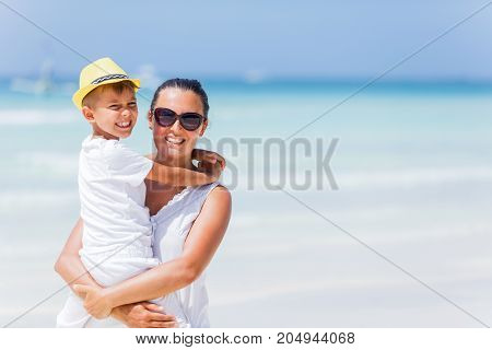 Mother with his son having fun at the white sand beach