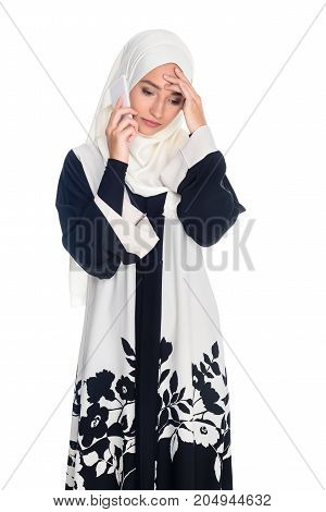 depressed young muslim woman talking by phone isolated on white
