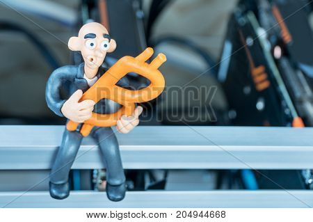 Bald plasticine businessman sits on a mining farm with bitcoin in his hand