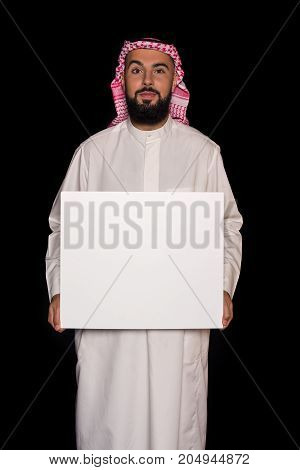 happy handsome muslim man holding blank board isolated on black