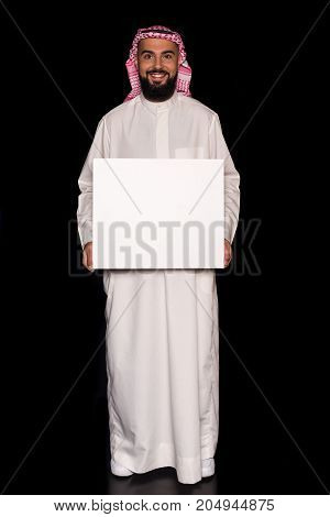 handsome muslim man holding blank board isolated on black