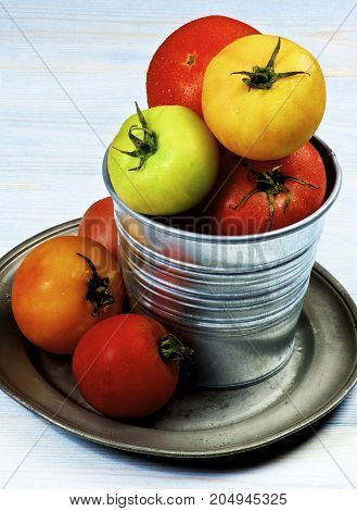 Arrangement of Colorful Fresh Tomatoes with Water Drops in Tin Bucket on Tin Plate closeup on Wooden background