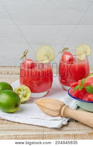 Watermelon fresh juice with mint leaves and lime citrus on wooden background