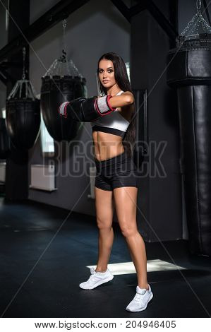 Portrait of a woman boxer aggressive and ready to fight. Punching Bag Punch.