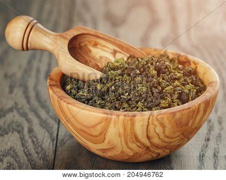 oolong green tea in wood bowl, on oak table