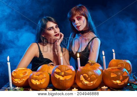 Two beautiful sexy witches with Halloween pumpkins over blue smoky background