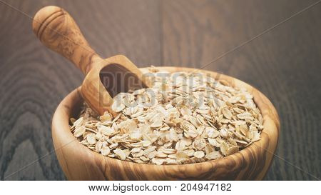 oat flakes in wood bowl on oak table, rustic style