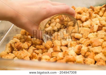 Close up hand scoops croutons in glass for cooking