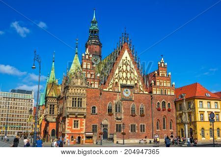 Wroclaw/Poland- August 17, 2017: Market Square - view of beautiful  gothic old Town Hall with tourists walking around, summer blue sky