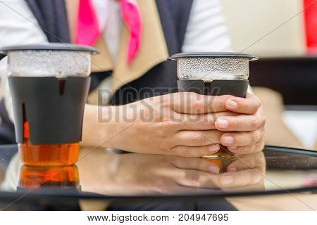 Close up woman's hand holding modern transparent tea cup made of glass