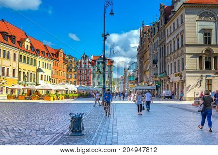 Wroclaw/Poland- August 17, 2017: cityscape of old town Market Square with colorful historical buildings, citizens ant tourists walking around