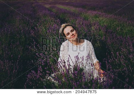 Smiling pregnant woman in white dress in lavender field.