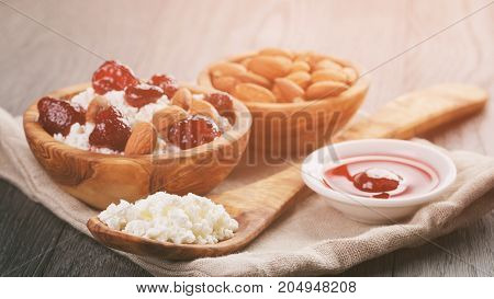 cottage cheese with preserved strawberry in wood bowl on oak table, selective focus