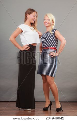 Fashionable style clothes concept. Woman wearing white top and long black shirt showing her leg standing next to older female with short striped dress