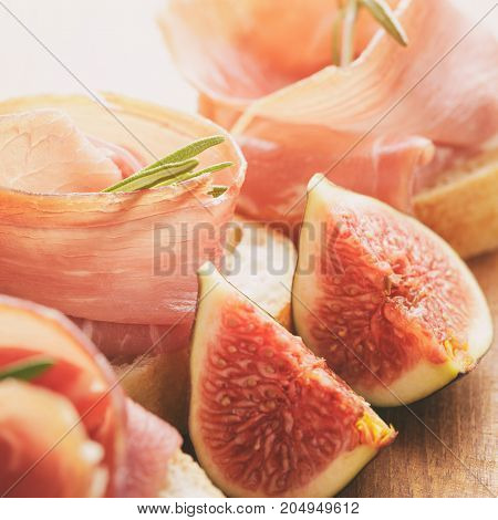 canapes with jamon and figs on wooden board, soft light