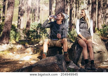 Hiking Couple Relaxing Sitting On Rocks During Trekking