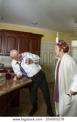 Drunk Man With Wife In Kitchen With Menacing Rolling Pin