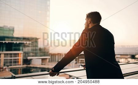 Businessman Standing In Airport Lounge Balcony And Looking Outsi