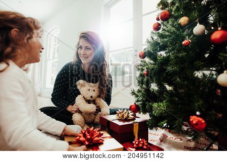 Mother with her child daughter celebrating Christmas. Young woman with her daughter sitting beside Christmas tree holding gift boxes.