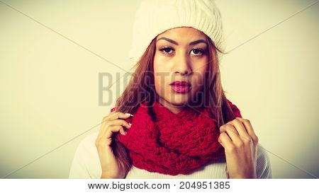 Winter clothing fashion concept. Beautiful young mulatto woman wearing red woolen scarf white cap. Mixed race girl in wintertime clothes portrait studio shot