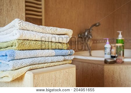 Close up pile of colorful towels lying in modern bathroom with cosmetics in background