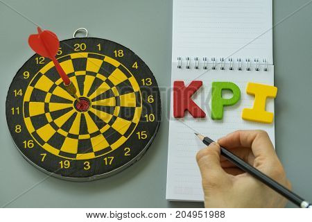 hand holding pencil and colorful alphabet KPI with dartboard as Goals or Target concept.